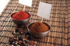 Two bowls of spices with price stickers and peppercorn Stock Image