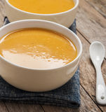 Two bowls of squash soup on wooden table Royalty Free Stock Photography