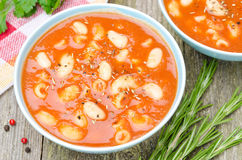 Two bowls of tomato soup with pasta, white beans and rosemary Stock Photos