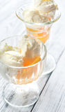Two bowls of vanilla ice cream with peaches. On the wooden table Stock Photo