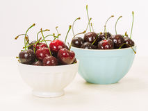 Two bowls of wet cherries Stock Images