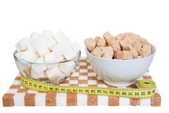 Two bowls with white and brown sugar on a stand of sugar and a m. Easuring tape Stock Images