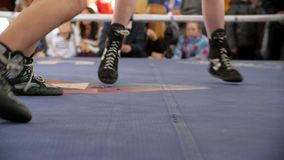 Two boxers fight in the boxing ring in boxing shoeses. Low section of male boxer standing against referee by athlete. Lying in boxing ring HD stock footage