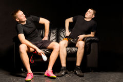 Two boxers having fun before a training session. Two young boxers having fun before a training session sitting on a black leather couch in the darkness laughing Royalty Free Stock Photos