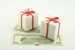 Two boxes on denominations. Two small white boxes with gifts on dollar denominations Royalty Free Stock Image