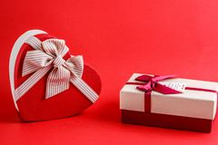 Two boxes of gifts with a ribbon on a red background. The concept is suitable for love stories, birthdays and Valentine`s Day.  royalty free stock photography