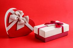 Two boxes of gifts with a ribbon on a red background. The concept is suitable for love stories, birthdays and Valentine`s Day.  royalty free stock photos