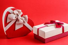 Two boxes of gifts with a ribbon on a red background. The concept is suitable for love stories, birthdays and Valentine`s Day.  stock photo