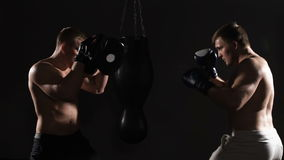 Two boxing men exercising together at the health club. Dark area stock video