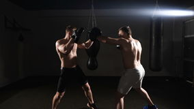 Two boxing men exercising together at the health club. Dark area stock video footage
