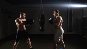 Two boxing men exercising together at the health club. Dark area stock footage