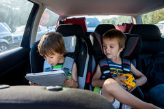 Two boy in children car seats, traveling by car and playing with Royalty Free Stock Image