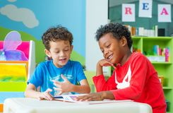 Two boy kid sit on table and reading tale book  in preschool lib Royalty Free Stock Photo
