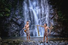 Two boy laugh fishing at a waterfall countryside thailand.Fishing boy asian by gaff in creek with beautiful background royalty free stock photos