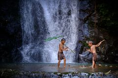 Two boy laugh fishing at a waterfall countryside thailand.Fishin. G boy asian by gaff in creek with beautiful background Stock Photo
