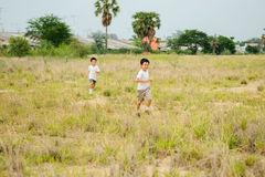 Two boy play on the dry field Stock Images