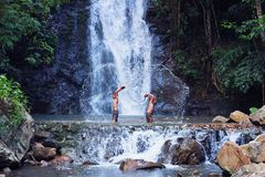 Two boy play and laugh fishing at a waterfall countryside thaila. Nd.Fishing boy asian by gaff in creek with beautiful background Royalty Free Stock Photography