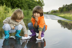 Two boy play in puddle Stock Image