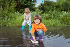 Two boy play in puddle Stock Photos