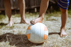 Two boy's legs standing beside soccer ball on. Picture of big ball on dried grass field in sunny day. Two boy's legs standing beside soccer ball on blurred Royalty Free Stock Photography
