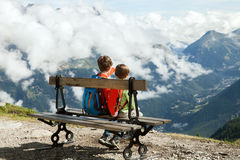 Two boy sit on bench in Alps Stock Photo
