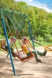 Two boy swinging on a swing in the park Stock Photography