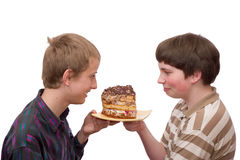 Two boys. Champing to eat a large piece of home-made cake Stock Photos