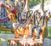 Two boys with admiration go for a drive on the carousel. Rostov-on-Don, Russia- May 29,2016: Two boys with admiration go for a drive on the carousel in the park Stock Photography