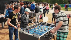 Two boys and adult men absorbedly play american table soccer. Summer festival stock video footage