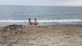 Two boys age 7-8 playing on the beach stock footage