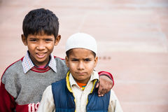 Two boys, Agra, India. Agra, India - 2015, January 10 : Two young boys, one wearing a muslim taqiyah,  in the Jama Masjid mosque courtyard of Agra, India Stock Photos