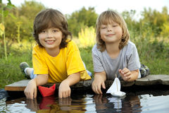 Two boys allowed paper boats from the pier of river Stock Image