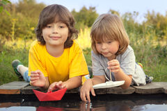 Two boys allowed paper boats from the pier of river Royalty Free Stock Photo