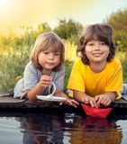 Two boys allowed paper boats from the pier of river Royalty Free Stock Photography