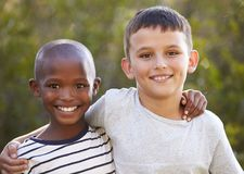 Two boys, arms around each other smiling to camera outdoors Stock Photos