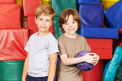 Two boys with ball in gym. Two boys standing with a ball in gym of a preschool stock photos