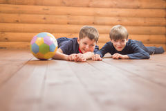 Two boys with a ball lying on the floor Stock Photo