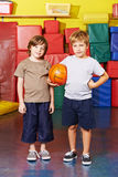 Two boys with basketball in gym of school Stock Image