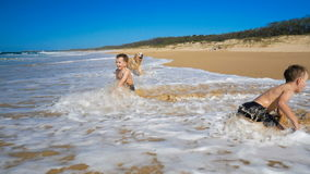 Two boys on the beach getting wet by the wave stock video footage
