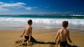 Two boys on the beach getting wet by the wave. Two happy twin boys on the beach getting wet by the wave stock footage