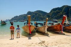 Two boys on the beach with Long tail boats royalty free stock photos
