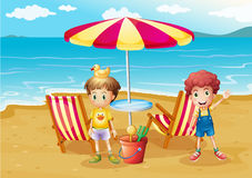 Two boys at the beach near the umbrella and chairs Royalty Free Stock Image