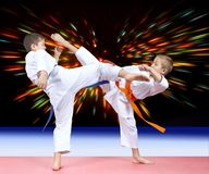 Two boys beat kicks in the background of bright rays Stock Photography