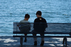 Two boys at a bench. Two friends talking Stock Photography