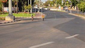 Two boys bike on empty city road stock video footage