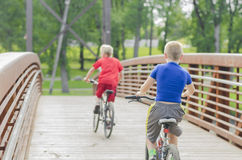 Two boys biking on bridge to North Dakota Royalty Free Stock Photography
