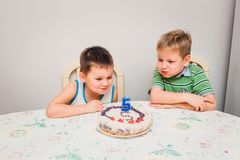 Two boys blow off the candle on the cake stock images