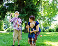 Two boys blowing bubbles. In park Royalty Free Stock Photos
