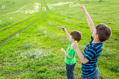 Two boys blowing up the soap bubbles on lawn Stock Photos