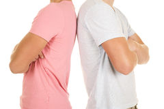 Two boys bodies back to back arms folded. Two teens with their backs to each other with their arms folded stock images